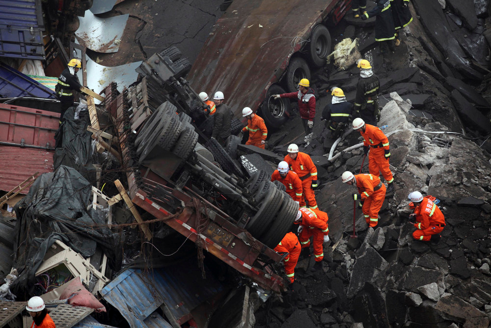 Description of . Rescuers work at the accident site where an expressway bridge partially collapsed due to a truck explosion in Mianchi County, Sanmenxia, central China's Henan Province, Thursday, Feb. 1, 2013. A truckload of fireworks intended for Lunar New Year celebrations went off Friday in a massive, deadly explosion that destroyed part of an elevated highway in central China, sending vehicles plummeting 30 meters (about 100 feet) to the ground. (AP Photo)