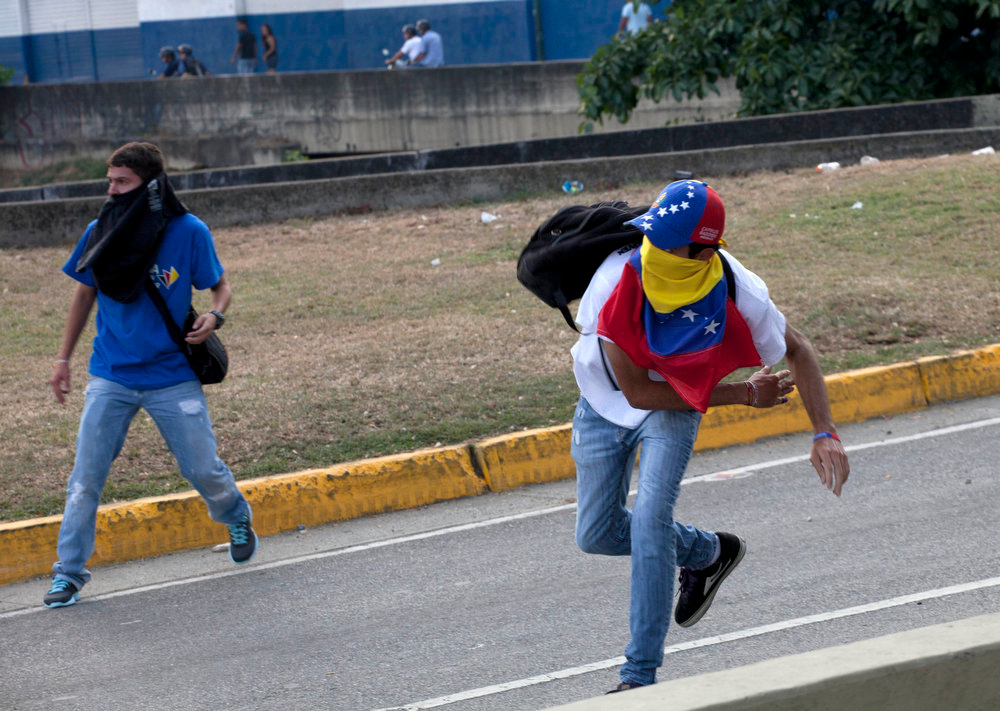 . Demonstrators throw stones at riot police as opposition supporters and students clashed with riot police while trying to block a highway in the Altamira neighborhood in Caracas, Venezuela, Monday, April 15, 2013. National Guard troops fired tear gas and plastic bullets to disperse students protesting the official results in Venezuela\'s disputed presidential election.   (AP Photo/Ramon Espinosa)
