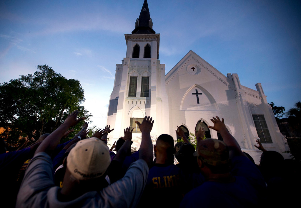 . The men of Omega Psi Phi Fraternity Inc. lead a crowd of people in prayer outside the Emanuel AME Church, Friday, June 19, 2015, after a memorial in Charleston, S.C. Thousands gathered at the College of Charleston TD Arena to bring the community together after nine people where shot to death at the church on Wednesday. The current brick Gothic revival edifice, completed in 1891 to replace an earlier building heavily damaged in an earthquake, was a mandatory stop for the likes of Booker T. Washington and the Rev. Martin Luther King Jr. Still, Emanuel was not just a church for the black community. (AP Photo/Stephen B. Morton)