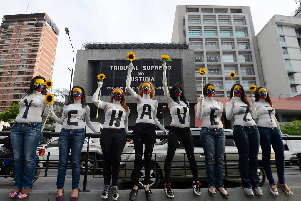 """. Students who support opposition political groups take part in a demonstration in Caracas March 4, 2013. Protesters are demanding proof that the cancer-stricken Venezuelan leader is still alive and governing. The words say \""""And Chavez?\"""" REUTERS/Stringer"""