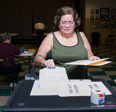 08/14/18 Wesley Bunnell | Staff Alida Santana-Figueroa enters her ballot into the machine at the St. Francis of Assisi Church Hall voting location on Tuesday afternoon.