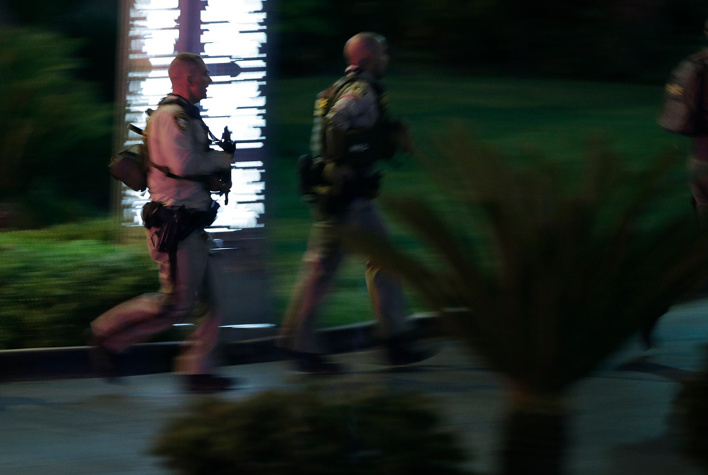 . Police officers rush into the Mandalay Bay resort and casino during a shooting near the casino on the Las Vegas Strip, Sunday, Oct. 1, 2017, in Las Vegas. (AP Photo/John Locher)