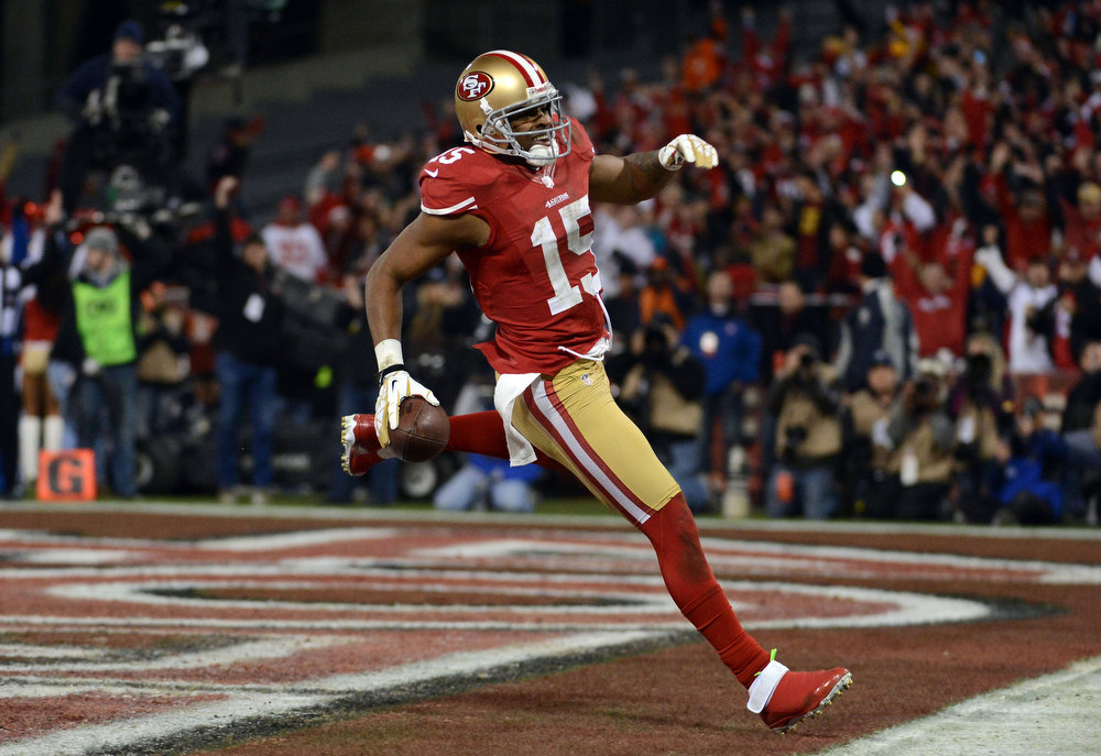 Description of . Wide receiver Michael Crabtree #15 of the San Francisco 49ers runs the ball in for a touchdown thrown by quarterback Colin Kaepernick #7 in the second quarter against the Green Bay Packers during the NFC Divisional Playoff Game at Candlestick Park on January 12, 2013 in San Francisco, California.  (Photo by Harry How/Getty Images)