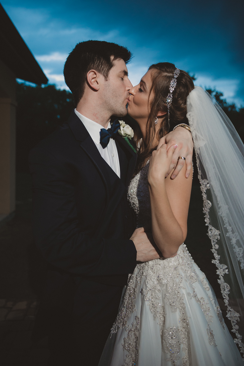 a bride and groom kissing at sunset on their wedding night