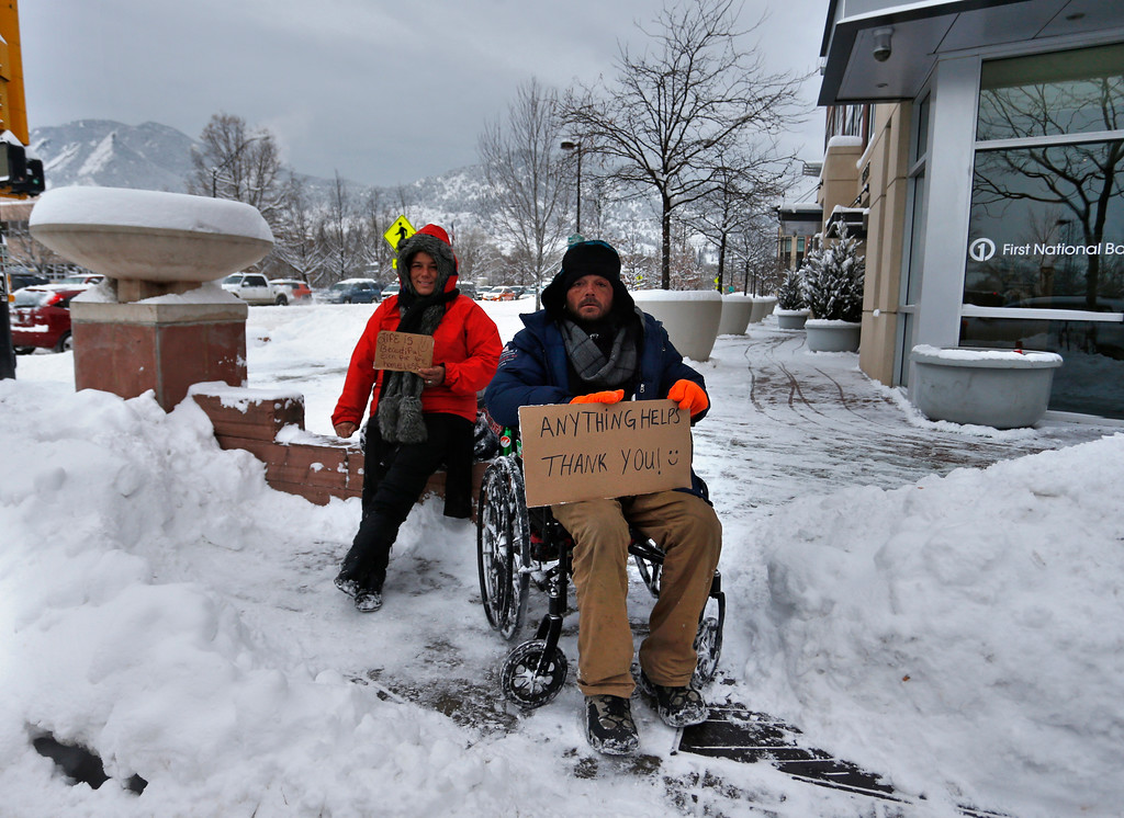 . Two homeless people wait at an intersection carrying signs and looking for help from passing motorists in Boulder, Colo., Thursday, Jan. 5, 2017. A winter storm dropped several feet of snow in the Colorado high country, and over a foot in Front Range communities. (AP Photo/Brennan Linsley)