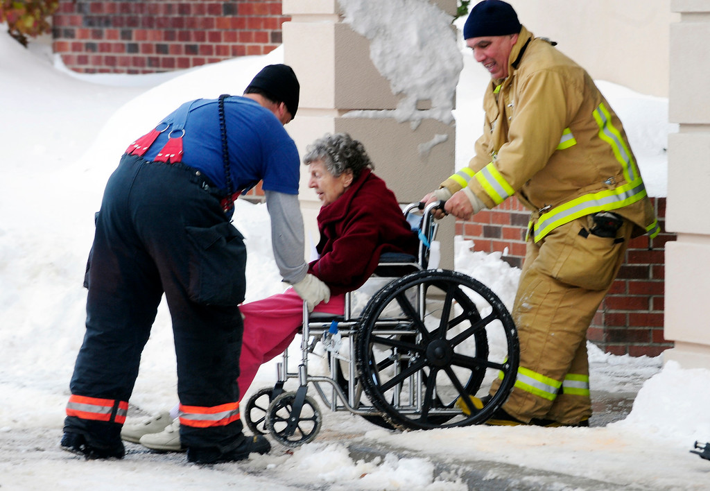 . Firefighters from Cheektowaga and Depew assist an elderly patient from from Garden Gate Health Care Facility to the Appletree Mall in Cheektowaga, N.Y.,  Thursday, Nov. 20, 2014. About 180 patients from the facility were moved after officials questioned sustainability of the the roof from the  snowfall.   Roofs began to creak and collapse under the weight of excessive snow as another storm Thursday added to epic snowfall in western New York state. (AP Photo/Gary Wiepert)