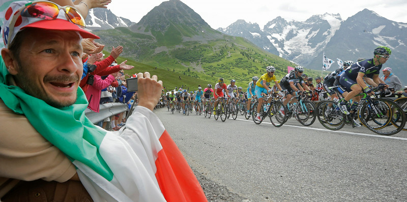 . A spectator draped in the Italian flag watches the pack with Italy\'s Vincenzo Nibali, wearing the overall leader\'s yellow jersey, pass the summit of Lautaret pass, French Alps, during the fourteenth stage of the Tour de France cycling race over 177 kilometers (110 miles) with start in Grenoble and finish in Risoul, France, Saturday, July 19, 2014. (AP Photo/Laurent Cipriani)