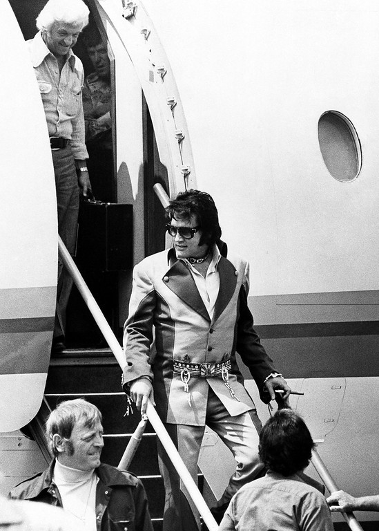 . Cigar in hand, Elvis Presley walks down the ramp after arriving in Charleston, West Virginia on July 11, 1975, for the first of three concerts in the West Virginia capital city. Elaborate security precautions kept Presley a safe distance away from the crowd which greeted him at the Kanawha Airport and at his downtown hotel. More than 18,000 tickets were sold for the concerts, one Friday at night and two Saturday. (AP Photo)