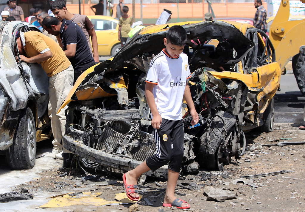 . Iraqis inspect damage at the site of a car explosion on May 13, 2014 in Baghdad\'s northern Shiite-majority district of Sadr City.  AFP PHOTO / AHMAD AL-RUBAYE/AFP/Getty Images