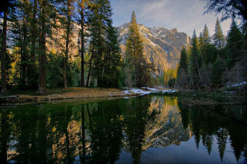 The fading sunlight made these mountains look almost like a painting. Yosemite in winter sunset-- Feb 13, 2010. This section of the Merced River has pooled up behind a natural dam of fallen trees, making the river mirror smooth.