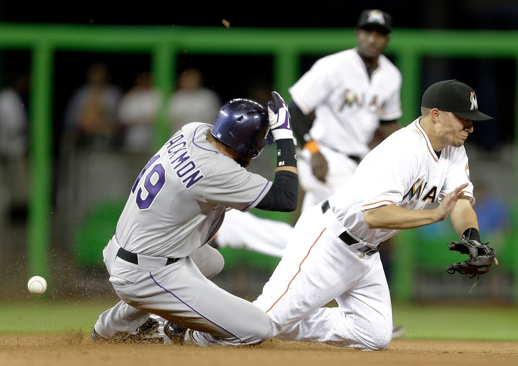 . Colorado Rockies\' Charlie Blackmon (19) beats the throw to Miami Marlins second baseman Jeff Baker, right, in the seventh inning of a baseball game, Tuesday, April 1, 2014, in Miami. The Marlins defeated the Rockies 4-3. (AP Photo/Lynne Sladky)
