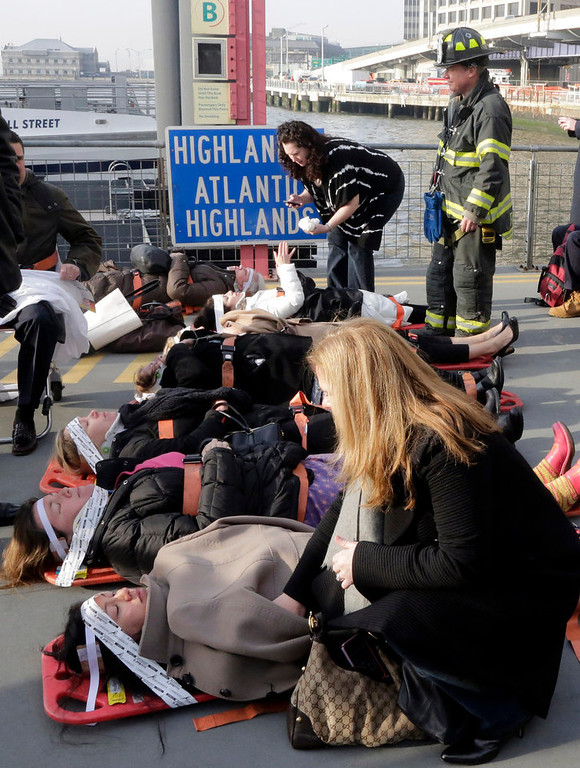. Injured passengers from the Seastreak Wall Street ferry wait to be taken to ambulances, in New York,  Wednesday, Jan. 9, 2013. The ferry from Atlantic Highlands, N.J., banged into the mooring as it arrived at South Street in lower Manhattan during morning rush hour, injuring as many as 50 people, at least one critically, officials said.(AP Photo/Richard Drew)