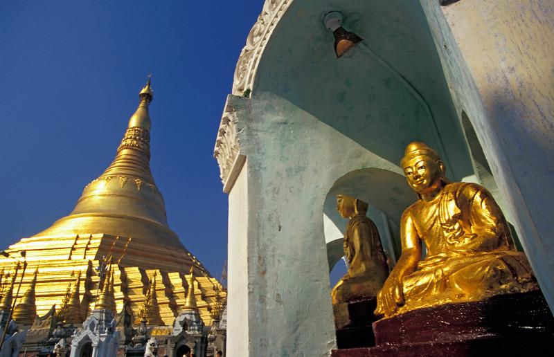 Golden Buddha Statue in front of Shwedagon Pagoda (Paya) Spire in Rangoon, Burma (Myanmar)
