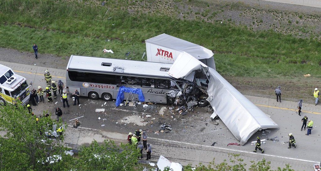 . Authorities investigate the scene of a fatal collision between a tractor-trailer and a tour bus on Interstate 380 near Mount Pocono, Pa., Wednesday, June 3, 2015. Multiple people were killed and more than a dozen were sent to hospitals. (AP Photo/David Kidwell)