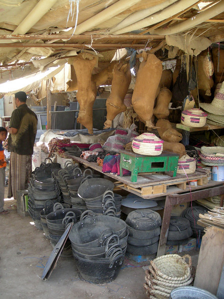 a Seiyun market shop selling recycled rubber baskets, animal bladder water containers, and woven goods