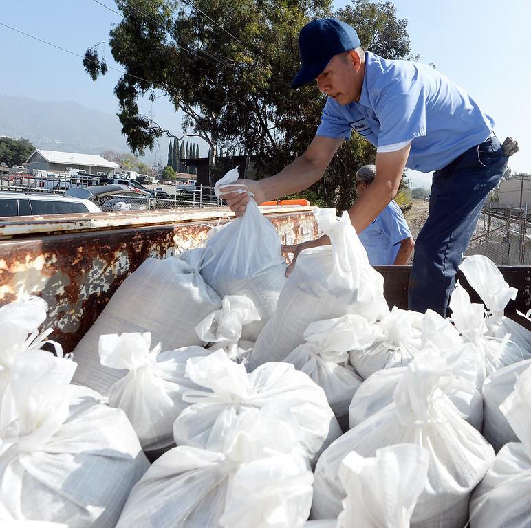 . St. Lucy\'s Priory High School employees Enrique Zavala loads sand bags into a truck at the Glendora city yard Tuesday February 25, 2014. Possible heavy rains in the coming days could create mud flows off of the burned hill sides caused by January\'s Colby Fire. (Will Lester/Inland Valley Daily Bulletin)