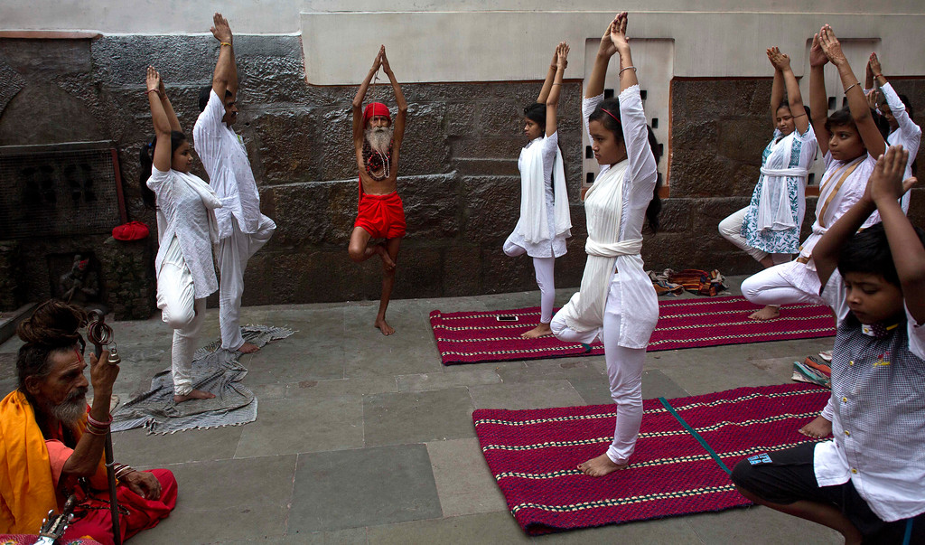 . An Indian Sadhu or Hindu holy man performs Yoga as others follow him to mark the International Yoga Day at Kamakhya temple in Gauhati, India , Wednesday, June 21, 2017.  Millions of yoga enthusiasts across India take part in a mass yoga sessions to mark the third International Yoga Day which falls on June 21 every year. (AP Photo/ Anupam Nath)