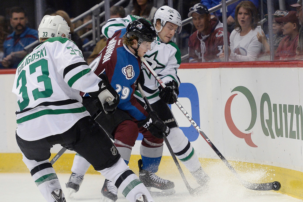 . Colorado Avalanche center Nathan MacKinnon (29) tangles with Dallas Stars defenseman Alex Goligoski (33) and left wing Ryan Garbutt (16) during the first period.  (Photo by AAron Ontiveroz/The Denver Post)