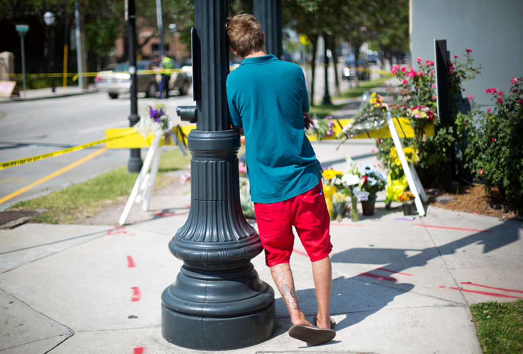 . A man leans against a light pole as he visits a makeshift memorial down the street from where a white man opened fire Wednesday night during a prayer meeting inside Emanuel AME Church killing several people in Charleston, S.C., Thursday, June 18, 2015. (AP Photo/David Goldman)