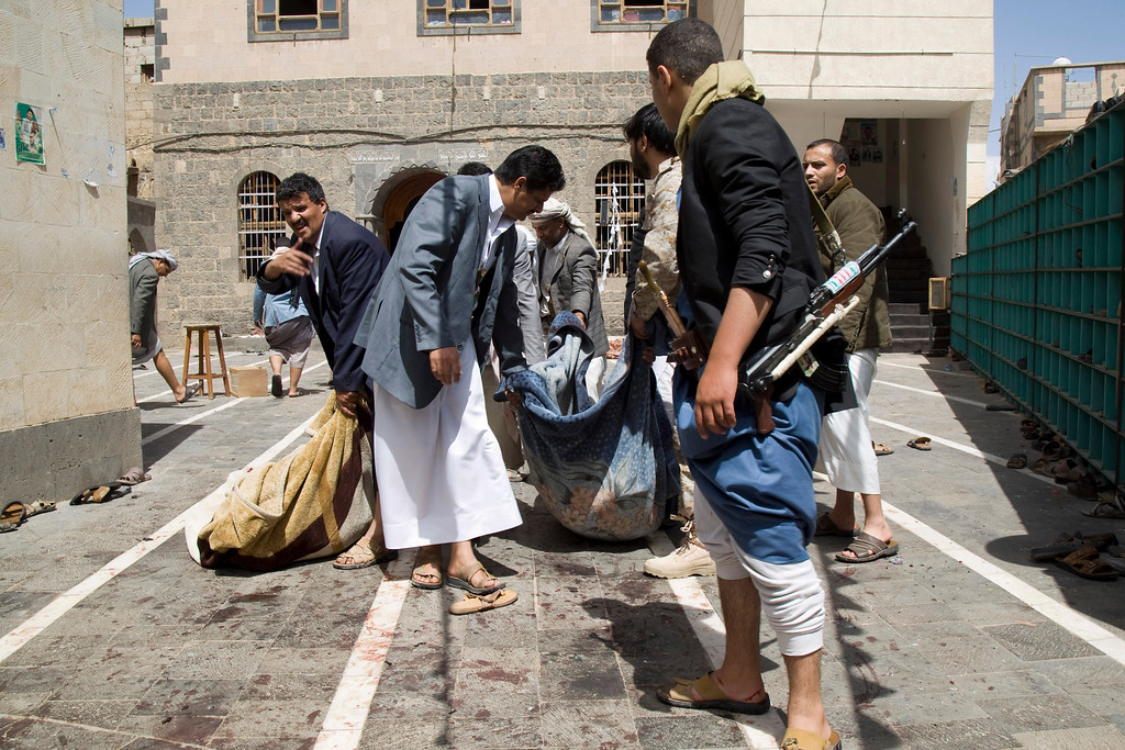 . Houthi fighters carry a body of a man killed in a suicide attack that struck a mosque in Sanaa, Yemen, Friday, March 20, 2015. Triple suicide bombers hit a pair of mosques crowded with worshippers in the Yemeni capital, causing heavy casualties, according to witnesses. The attackers targeted mosques frequented by Shiite rebels, who have controlled the capital since September. (AP Photo/Hani Mohammed)
