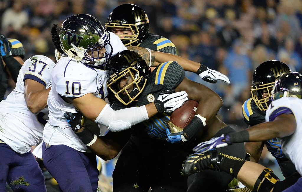 . UCLA Bruin running back Myles Jack (30) scores one of his four touchdowns against the Washington Huskies during the first half of their college football game in the Rose Bowl in Pasadena, Calif., on Friday, Nov. 15, 2013.   (Keith Birmingham Pasadena Star-News)