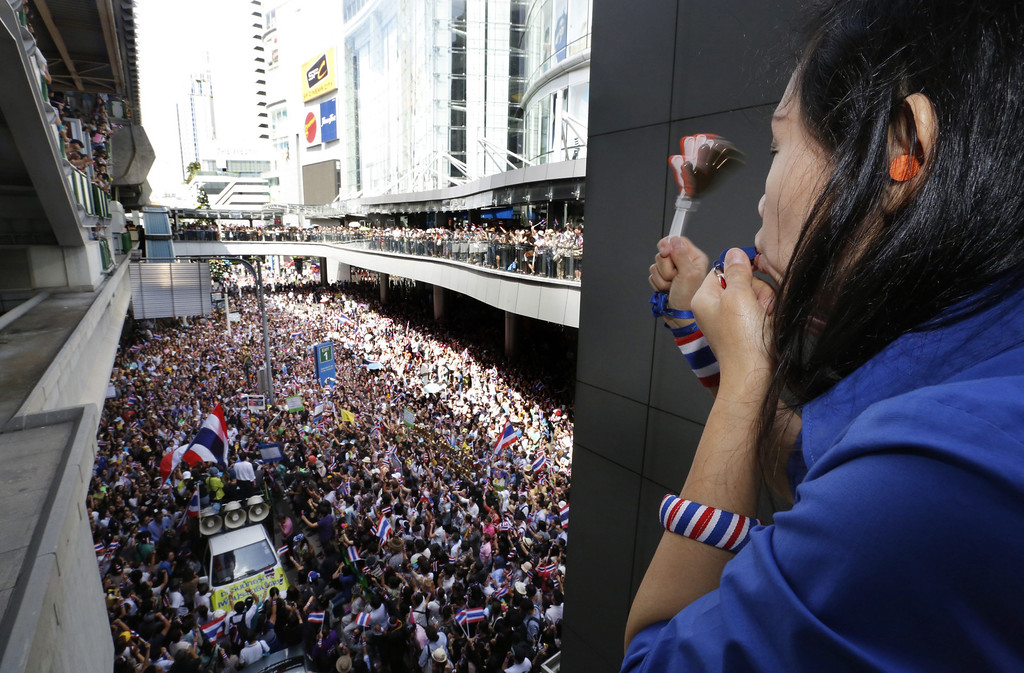 . Blowing her whistle from above, a Thai anti-government protester joins the rally at the start of a march on the US embassy in Bangkok, Thailand, 29 November 2013. Fears are increasing that tourism will be effected by the continuing protests.  EPA/BARBARA WALTON