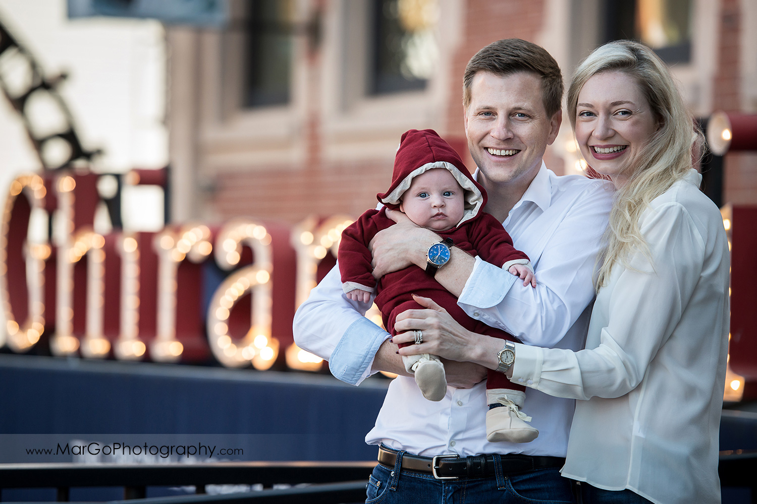 portrait of family of 3 in front of Ghirardelli sign in San Francisco