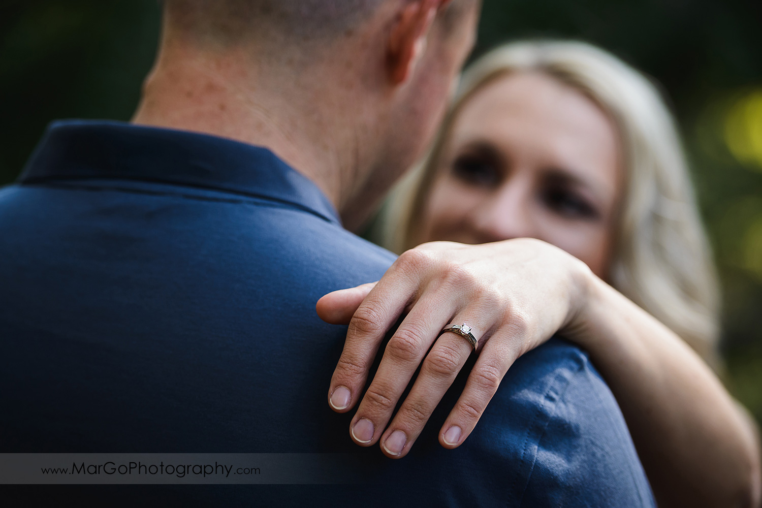 ring shot of woman holding hand on arm of man in navy blue shirt during engagement session at San Francisco Golden Gate Park