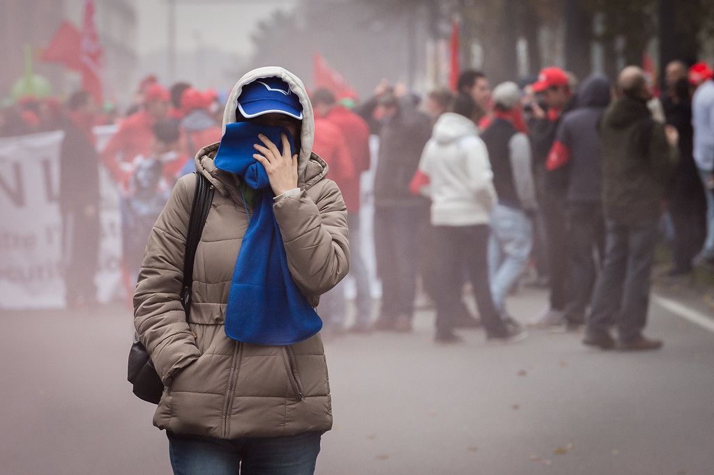 . A woman protects her face with a scarf during a national trade union demonstration in Brussels, Thursday Nov. 6, 2014. T (AP Photo/Geert Vanden Wijngaert)