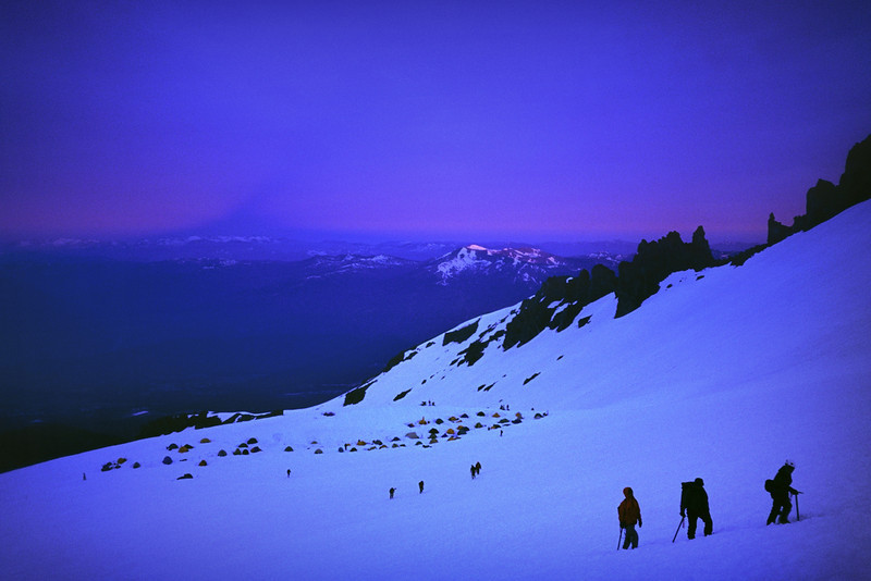 Climbers make their way to the summit from base camp at Helen Lake as the mountain casts its shadow on the far horizon at sunrise. Mount Shasta, CA    Summit Elevation: 14,162 ft.