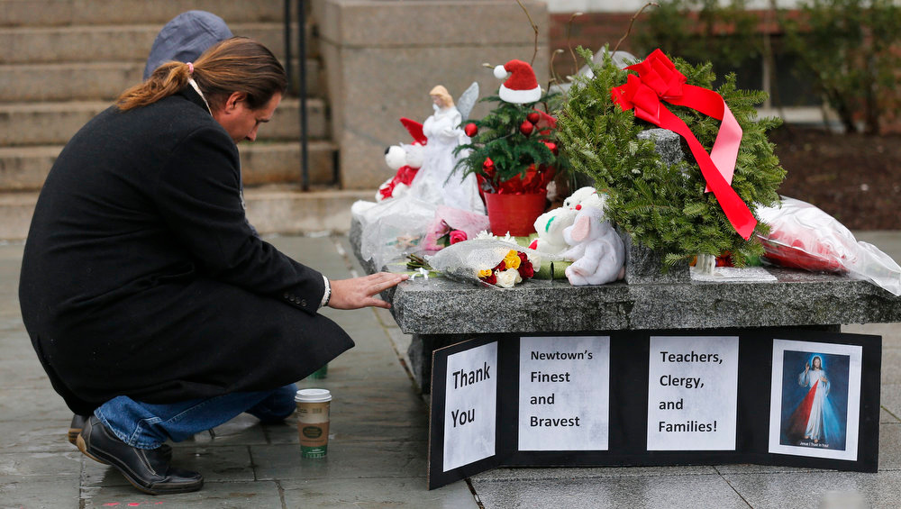 Description of . A couple pause at a memorial outside town hall in Newtown, Conn., Monday, Dec. 17, 2012. A gunman opened fire at Sandy Hook Elementary School in the town, killing 26 people, including 20 children before killing himself on Friday. (AP Photo/Charles Krupa)