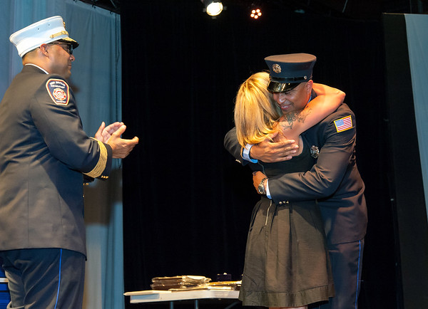 09/20/18 Wesley Bunnell | Staff The New Britain Fire Department held their 2018 Awards Ceremony on Thursday September 20 at Trinity on Main. Linda Ugarte hugs her son Firefighter Alexander Ugarte during the badge pinning ceremony as Fire Chief Raul Ortiz looks on.