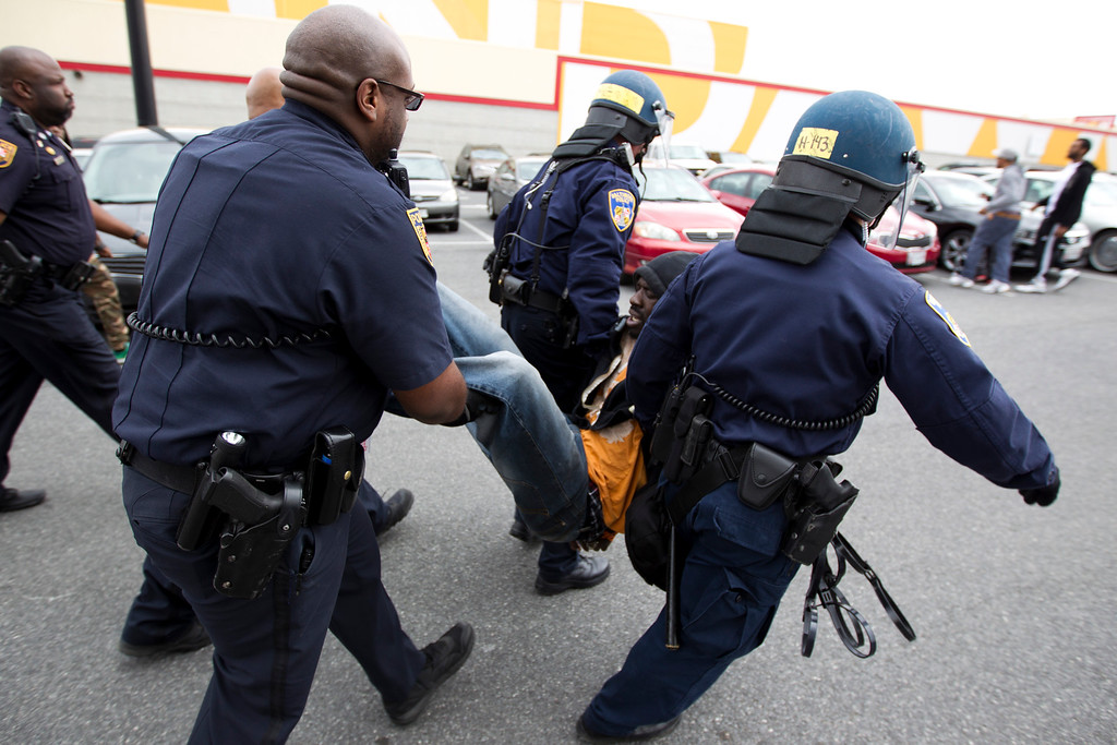 . Baltimore police officers detain a demonstrator after clashes with police, after the funeral of Freddie Gray, Monday, April 27, 2015, at New Shiloh Baptist Church in Baltimore. Gray died from spinal injuries after he was arrested and transported in a Baltimore Police Department van. (AP Photo/Jose Luis Magana)