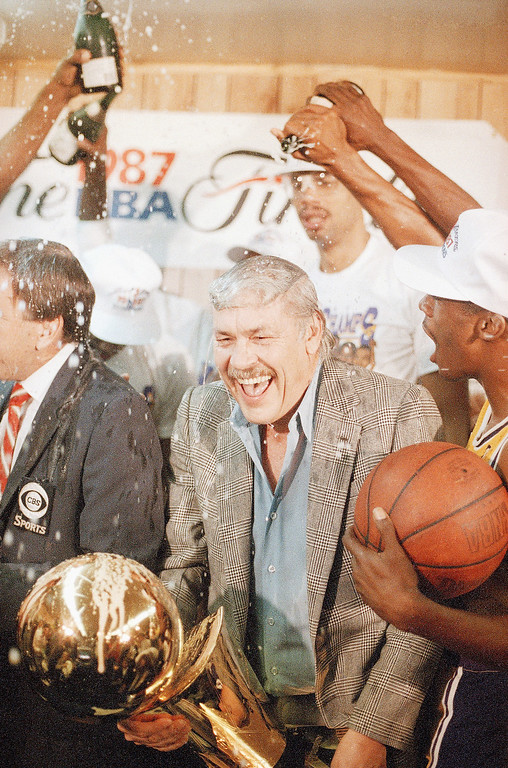 . Los Angeles Lakers owner Jerry Buss gets doused with champagne from members of his team as he holds the NBA Championship trophy Sunday, June 15,1987 after the Lakers defeated the Boston Celtics 106-93 to win the NBA Championship four games to two in Inglewood, Calif. (AP Photo/Lennox Mclendon)