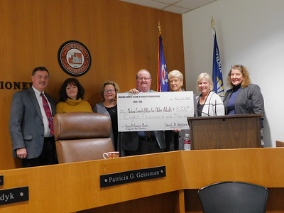 Senior Walk officials present check to county