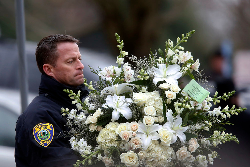 Description of . A police officer carries flowers into a funeral service for 6-year-old Noah Pozner, Monday, Dec. 17, 2012, in Fairfield, Conn. Pozner was killed when a gunman walked into Sandy Hook Elementary School in Newtown Friday and opened fire, killing 26 people, including 20 children. (AP Photo/Jason DeCrow)