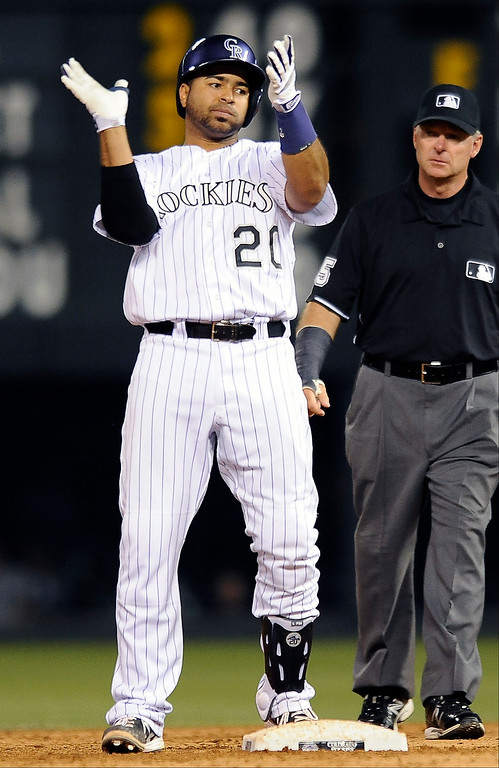 . Colorado Rockies\' Wilin Rosario, left, celebrates an RBI-double in the sixth inning of a baseball game against the San Diego Padres, Thursday, June 6, 2013, in Denver. (AP Photo/Chris Schneider)