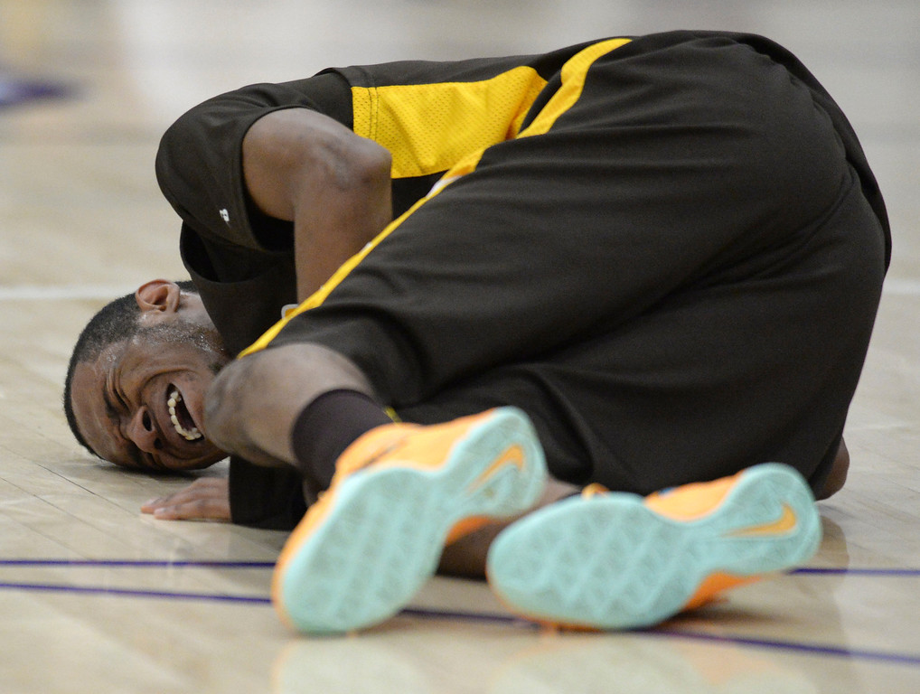 . Spartans\' senior guard Domenik Brewer fell to the court with a cramp in the third quarter. Photo By Karl Gehring/The Denver Post