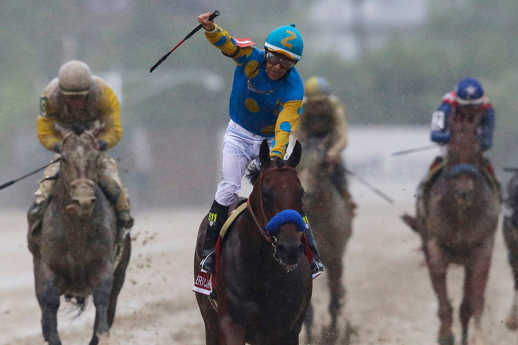 . American Pharoah, ridden by Victor Espinoza, center, celebrates after winning the 140th Preakness Stakes horse race at Pimlico Race Course, Saturday, May 16, 2015, in Baltimore. (AP Photo/Patrick Semansky)