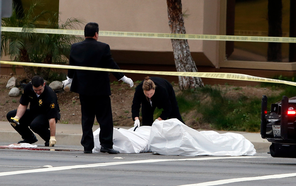 . Orange County coroner\'s officials remove a body from the scene in Orange, Calif., Tuesday, Feb. 19, 2013.County. (AP Photo/Jae C. Hong)