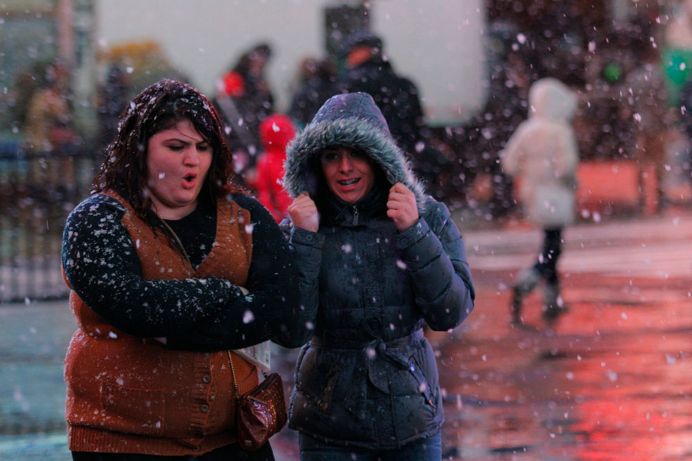 . People walk in a winter storm as snow falls at Times Square in New York, December 26, 2012. The severe winter weather that hit parts of the central and southern United States on Christmas Day moved eastward on Wednesday, causing flight delays and dangerous road conditions in the Northeast and Ohio Valley. REUTERS/Eduardo Munoz