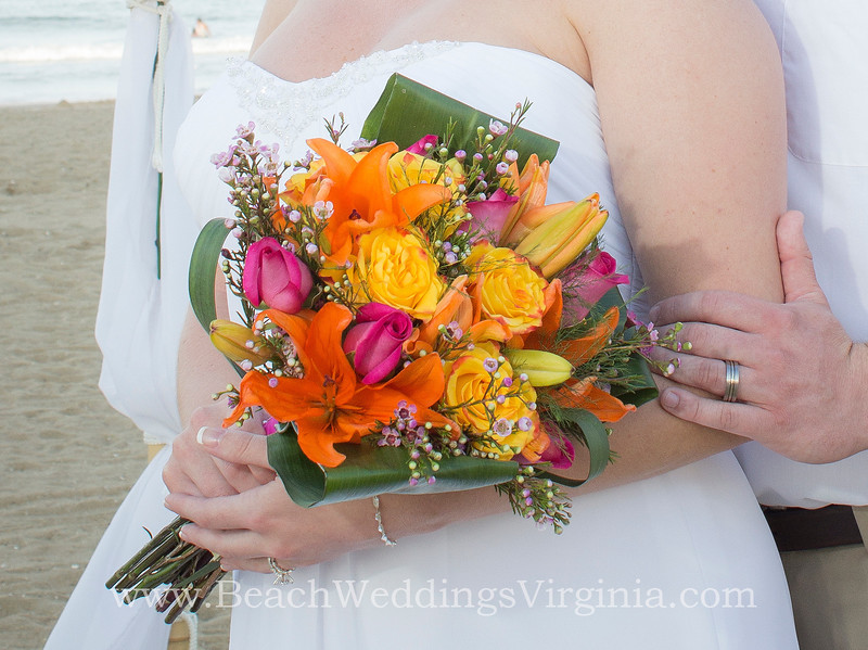 orange lilies, yellow roses (w red tips), hot pink accents, stems tied