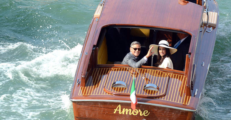 . George Clooney, flanked by his wife Amal Alamuddin, waves from a water-taxi after leaving the city hall in Venice, Italy, Monday, Sept. 29, 2014. George Clooney married human rights lawyer Amal Alamuddin Saturday, the actor\'s representative said, out of sight of pursuing paparazzi and adoring crowds. (AP Photo/Luigi Costantini)