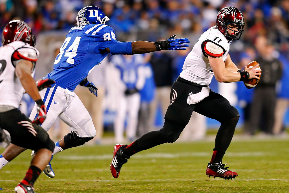 . Cincinnati\'s Brendon Kay (11) scrambles as Duke\'s Kenny Anunike (84) pursues during the first half of the Belk Bowl NCAA college football game in Charlotte, N.C., Thursday, Dec. 27, 2012. (AP Photo/Chuck Burton)