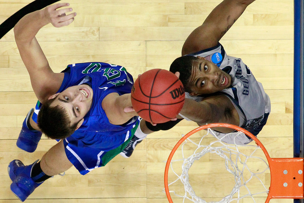 . Florida Gulf Coast\'s Chase Fieler, left, and Georgetown\'s Mikael Hopkins leap for a rebound during the first half of a second-round game of the NCAA college basketball tournament on Friday, March 22, 2013, in Philadelphia. (AP Photo/Matt Rourke)