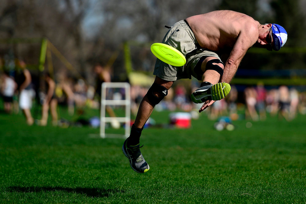 . Jonathan Willett performs a double spinning gitis as he catches the disc while playing freestyle frisbee with Larry Imperiale at Washington Park. Temperatures reached the low 80s in Denver. (Photo by AAron Ontiveroz/The Denver Post)