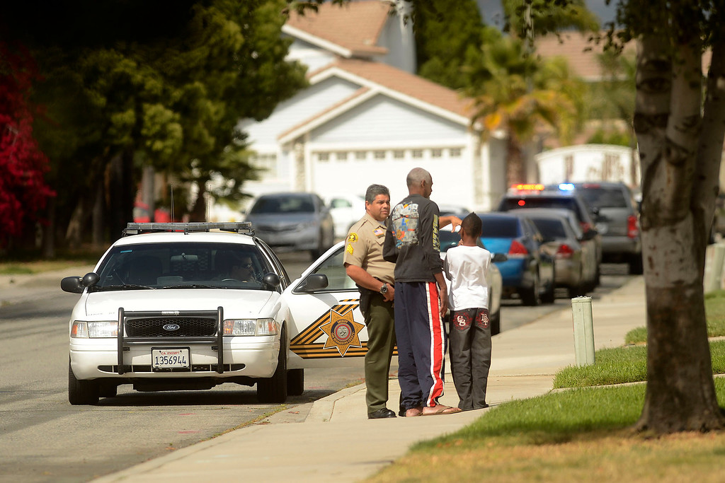 . Residents are briefed by San Bernardino County Sheriff\'s Deputies as police search for pursuit suspects along the 100 block of East Meadow Lane in Rialto April 16, 2013.   GABRIEL LUIS ACOSTA/STAFF PHOTOGRAPHER.