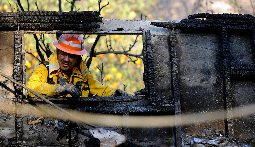 . A Los Angeles County fire capt. out of San Dimas looks through a burned out window at the Singer Estate Kregmont Dr. during the Colby Fire, a 1,700-acre plus brush fire that ignited in the Angeles National Forest north of Glendora  threatening homes and prompting mandatory evacuations in Glendora, Calif., on Thursday, Jan. 16, 2014. (Keith Birmingham Pasadena Star-News)