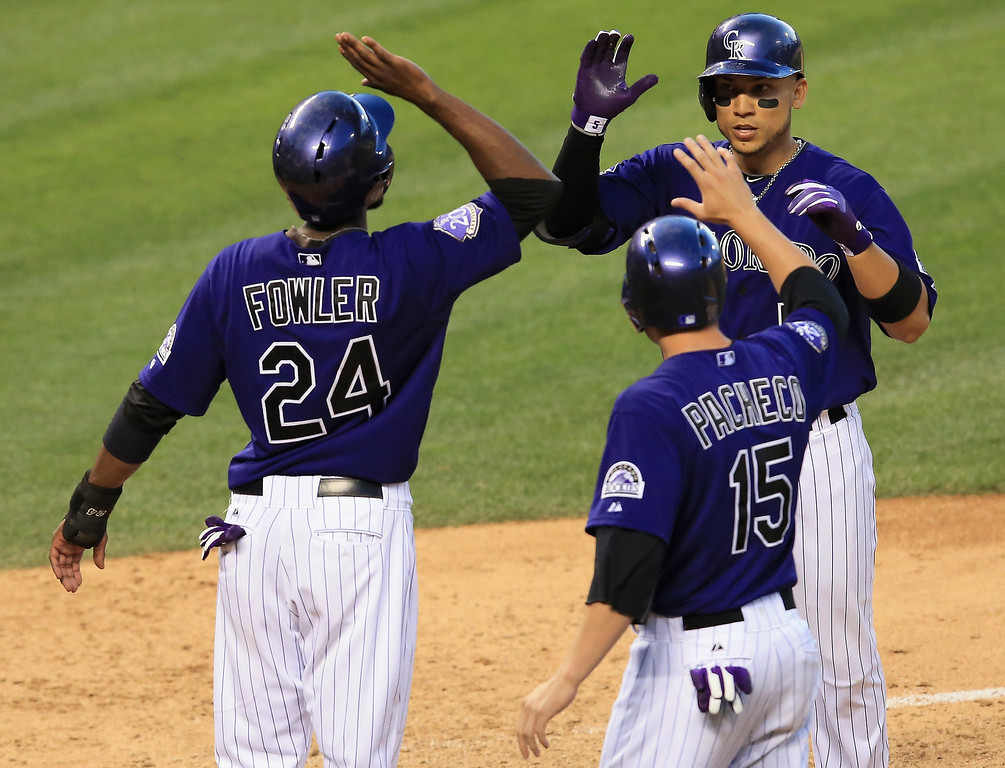 . Carlos Gonzalez #5 of the Colorado Rockies celebrates his three ru home run off of starting pitcher Dan Haren #15 of the Washington Nationals with Dexter Fowler #24 of the Colorado Rockies and Jordan Pacheco #15 of the Colorado Rockies who scored on the play as the Rockies took a 5-2 lead in the fifth inning at Coors Field on June 11, 2013 in Denver, Colorado.  (Photo by Doug Pensinger/Getty Images)