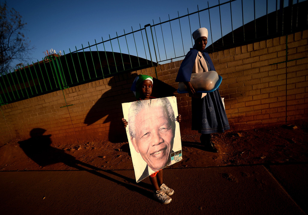 . A woman and a little girl hold a Nelson Mandela picture in front of the Medi Clinic Heart hospital in Pretoria on July 3, 2013. Emotional crowds gathered outside the hospital where Nelson Mandela lay in critical condition, as relatives and clan elders made preparations for the revered former South African leader\'s final journey. Singing supporters amassed outside the Pretoria hospital where the 94-year-old anti-apartheid hero was fighting for his life.  FILIPPO MONTEFORTE/AFP/Getty Images